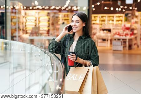 Young successful female customer with drink and paperbags talking on mobile phone after visiting departments of large modern mall