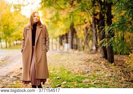 The Setting Sun. Calm Woman In Coat Standing On A Footpath In Autumn Park. Nature Walks.