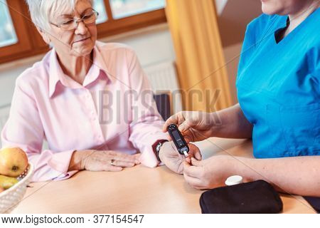 Nurse administers diabetes test to senior woman in nursing home