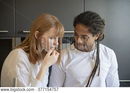 Focused Beautiful Woman Touching Her Lips While A Handsome Black Man Looks At Her Lovingly On An Out