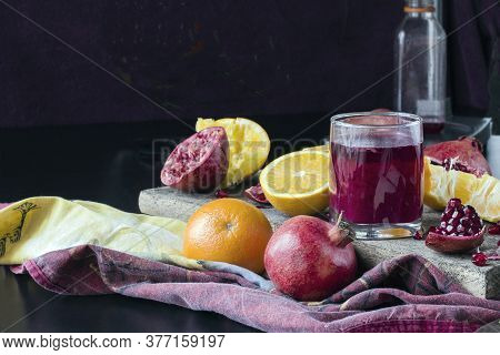 Glass Of Freshly Squeezed Pomegranate Juice, Sliced Fresh Fruit Into Pieces, The Process Of Squeezin