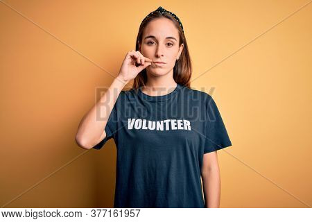 Young beautiful woman wearing volunteer t-shirt doing volunteering over yellow background mouth and lips shut as zip with fingers. Secret and silent, taboo talking