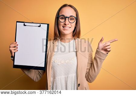 Beautiful inspector woman wearing glasses holding checklist clipboard over yellow background very happy pointing with hand and finger to the side