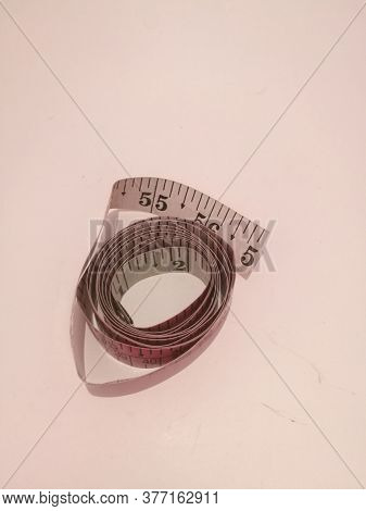 Top Angle View Of A Tailoring Tape Placed Isolated In A White Background.the Tape Has Markings On It