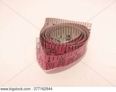 A Closeup View Of Tailoring Tape Placed Isolated In A White Background.the Tape Has Markings On It.t