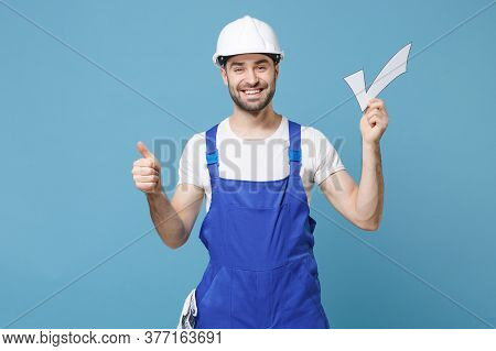 Smiling Young Man In Coveralls Protective Helmet Hardhat Hold Check Mark Isolated On Blue Wall Backg