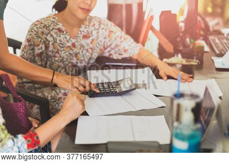 Woman Calculating Bills Using Calculator On Wooden Table.