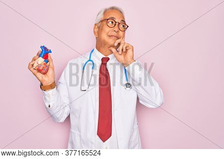 Middle age senior grey-haired cardiologist doctor man holding professional medicine heart serious face thinking about question, very confused idea