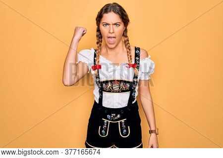 Young beautiful blonde german woman with blue eyes wearing traditional octoberfest dress angry and mad raising fist frustrated and furious while shouting with anger. Rage and aggressive concept.
