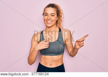 Young beautiful blonde sportswoman with blue eyes doing exercise wearing sportswear smiling and looking at the camera pointing with two hands and fingers to the side.