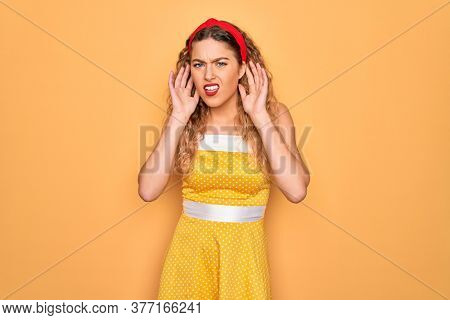 Beautiful blonde pin-up woman with blue eyes wearing diadem standing over yellow background Trying to hear both hands on ear gesture, curious for gossip. Hearing problem, deaf