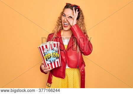 Beautiful blonde woman with blue eyes eating salty popcorn snack over yellow background with happy face smiling doing ok sign with hand on eye looking through fingers