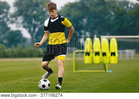 Young Teenage Soccer Player On Training Field Kicking Soccer Ball. Youth Sports Player Running On Gr