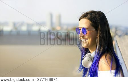 Close - Up Portrait Of A Young Beautiful Happy Girl With Blue Hair In Sunglasses And With Big Headph
