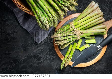 Asparagus. Fresh raw organic green Asparagus sprouts closeup. On black table background. Healthy vegetarian food. Raw vegetables, market. Healthy eating concept, diet, dieting. Top view, flat lay.