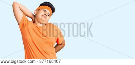 Little boy kid wearing sportswear suffering of neck ache injury, touching neck with hand, muscular pain