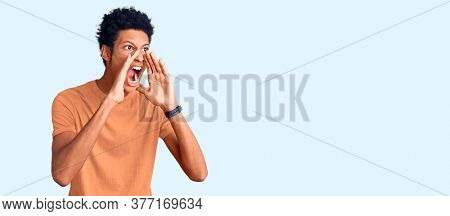 Young african american man wearing casual clothes shouting angry out loud with hands over mouth