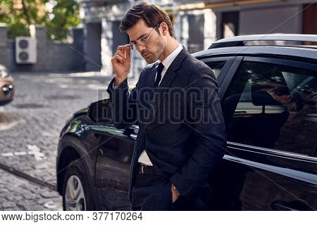 Side View Of Confident Business Man In Formalwear Adjust His Eyewear , Leaning At The Car And Lookin
