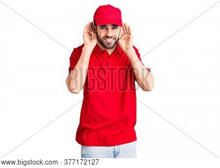 Young handsome man with beard wearing delivery uniform trying to hear both hands on ear gesture, curious for gossip. hearing problem, deaf