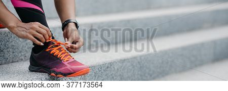 Morning Run In City. African American Girl With Fitness Tracker Ties Shoelaces On Fashionable Sneake