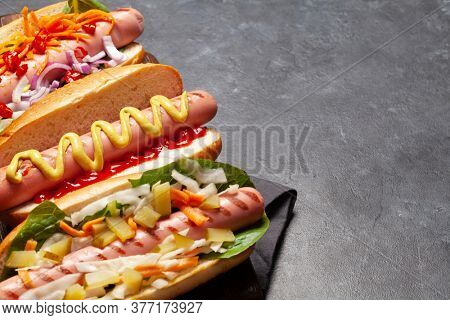 Various hot dog with vegetables, lettuce and condiments on stone background. With copy space