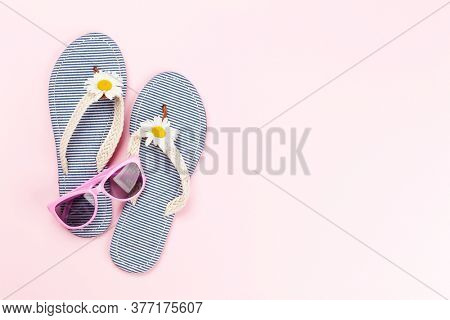 Beach flip flops with flowers and sunglasses on pink background. Summer vacation concept. Flat lay with copy space