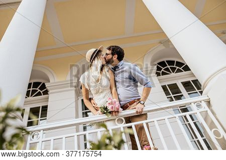 Close Up Of Stylish Couple In Embrance On Quay With Nature Background. Girl In White Dress With Pink