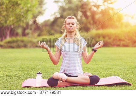 Young Sporty Woman With Eyes Closed Meditating In Padmasana Lotus Pose On Yoga Mat In Park At Sunset