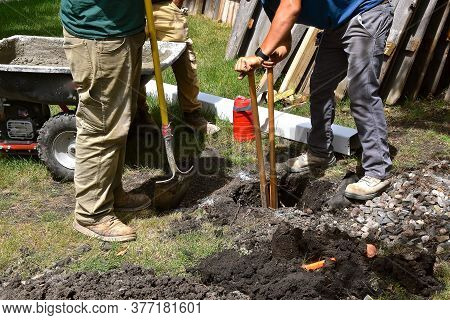 A Split Handled Post Hole Digger Is Moving The Necessary Dirt To Support A Post