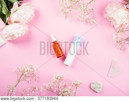 Pink Background With Skin Care Products Generic Bottles And Floral Decor. Flat Lay