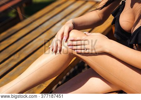 Sexy Girl Putting Sunscreen Lotion On Her Legs, Close Up. Woman Using Oil Spray Tanning Her Legs Pro