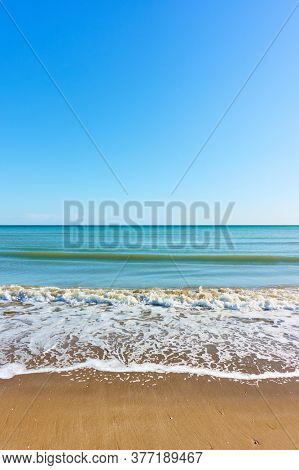 Vew of the sea beach with surf and cloudless blue sky, may be used as background