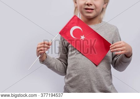 Child Holds The Flag Of Turkey. Close Up. Learning Turkish For Children. Immigration To Turkey.