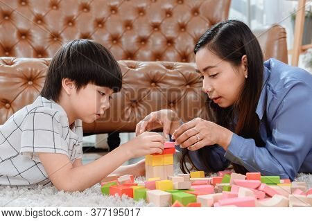 Asian Mother Work Home Together With Son. Mom And Kid Play Color Wooden Block. Child Creating Buildi