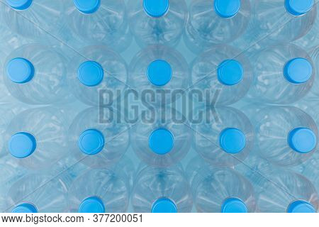 Horizontal Color Image With An Overhead View Of An Empty Clear Plastic Bottles With Caps Stacked On