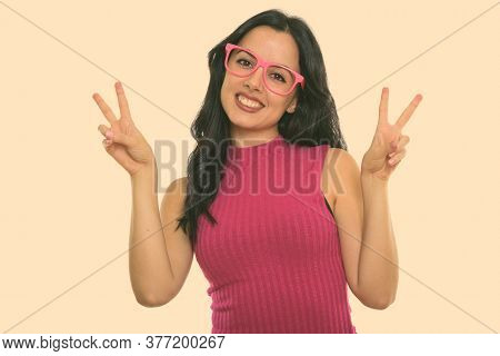 Studio Shot Of Young Happy Spanish Woman Smiling While Giving Peace Sign With Both Hands
