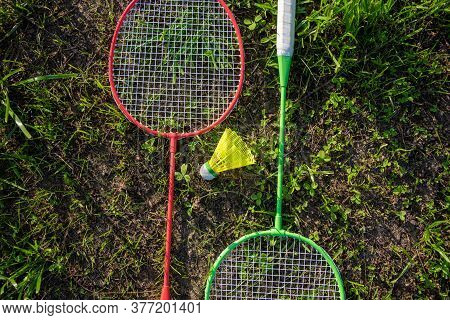 Two Badminton Rackets With A Yellow Shuttlecock On The Green Grass, Summer Active Games