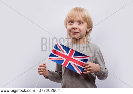 Exciting Fair-haired Boy Holding Flag Of Uk. Learning English For Children. Education In United King
