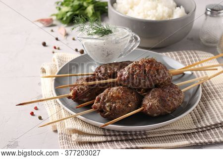 Kofta Kebab On Wooden Skewers On A Plate With Sauce And A Side Dish Of Rice On The Table, Traditiona