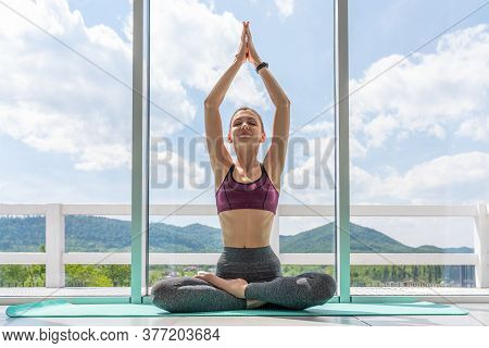 Charming Young Female Yoga Instructor Doing A Lotus Posture At The Beginning Of A Complex Of Exercis