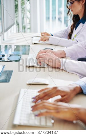 Close-up Image Of Scientists Or Doctors Working On Computers And Enterirng Results Of Research