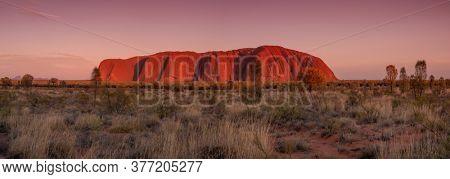 ULURU, AUSTRALIA - JANUARY 2020: Panoramic view of the Ayers Rock during summer sunset, Uluru, Northern Territory, Australia