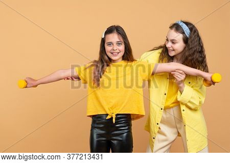 Young Beautiful Brunette Girl Showing How To Use Dumbbels To Her Little Sister. Healthy Active Lifes