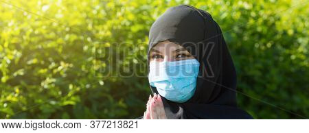 Muslim Girl In A Protective Medical Mask Prays To God. Muslim Girl In Protective Medical Mask Prays