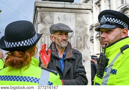 London - October 18, 2019: Close Up Of Extinction Rebellion Protester With Red Painted Hand Surround