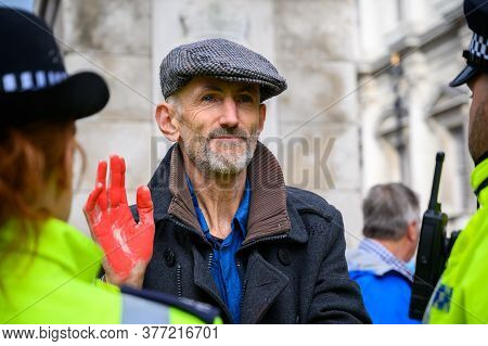 London - October 18, 2019: Close Up Of Male Extinction Rebellion Protester With Red Painted Hand Sur