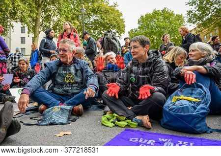 London - October 18, 2019: Mature Extinction Rebellion Protesters With Red Painted Hands Sat On A Ro
