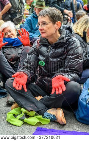 London - October 18, 2019: Middle Aged Female Extinction Rebellion Protester With Red Painted Hands
