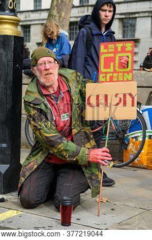London - October 18, 2019: Vertical Shot Of A Mature Male Extinction Rebellion Protester Holding Hom