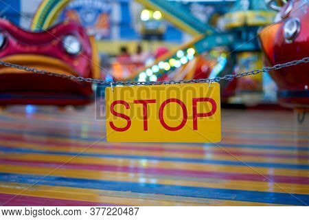 Stop Sign With Carnival Festival Blurred Carousel Background Amusement Park Closed Quarantine. Accid